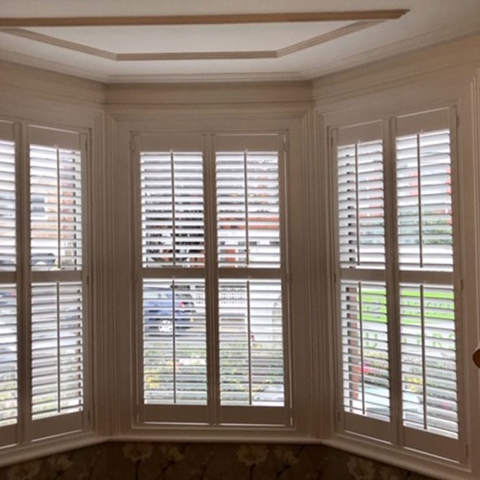 White plantation shutters in bay window with lamp shade