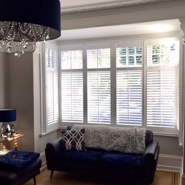 Grey living room with white plantation shutters in bay window