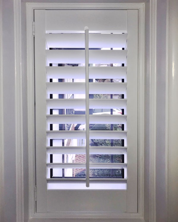 Half open plantation shutters in small window area