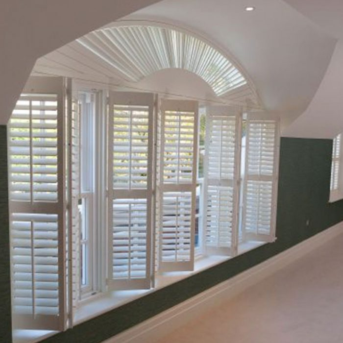 Foldable white wooden shutters half open with green walls