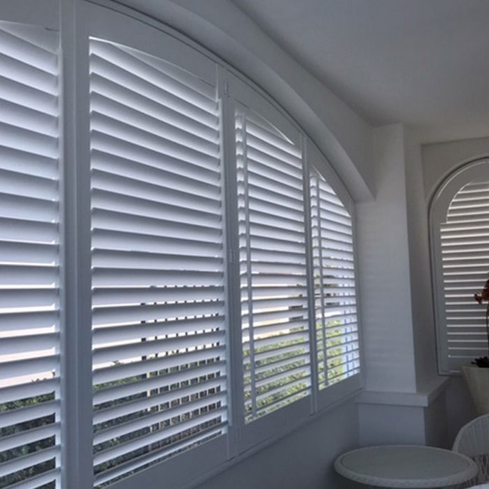 Arched white plantation shutters half open