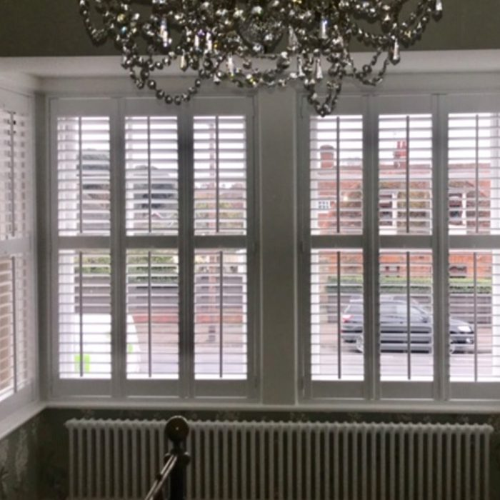 Crystal light hanging with white plantation shutters