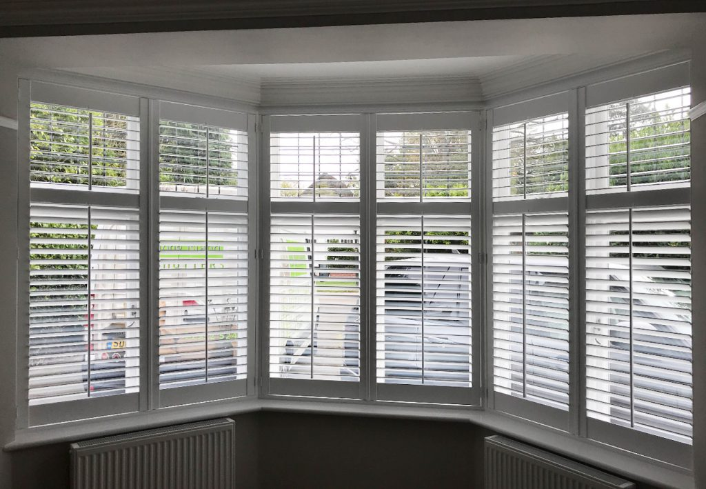 6 panels of plantation shutters open in bay window