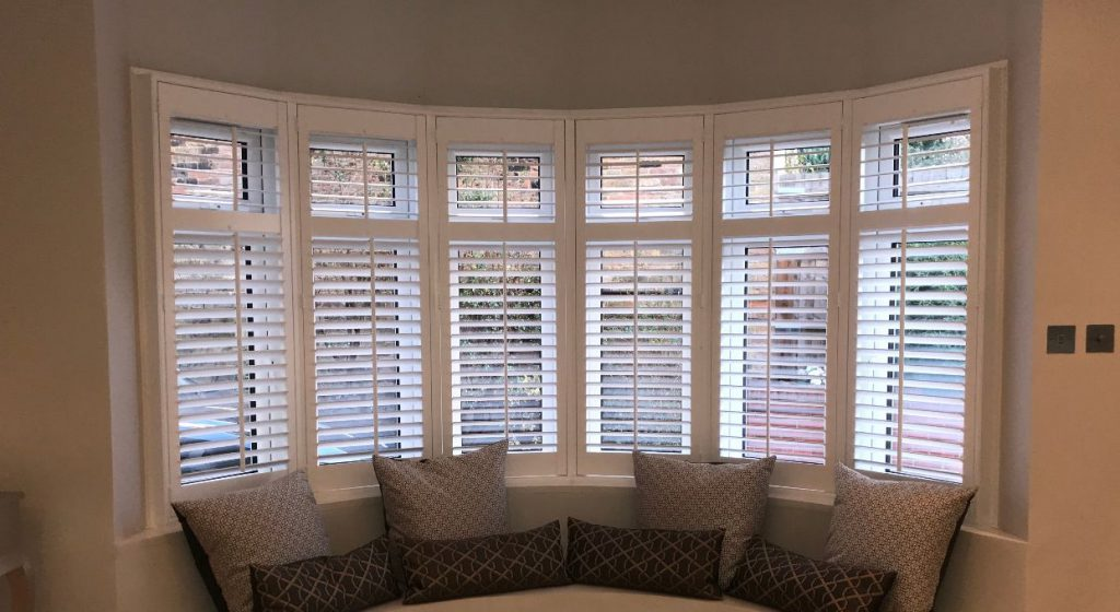White wooden shutters fitted to curved bay window area