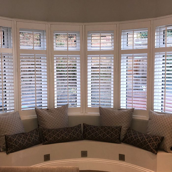 Curved seating area in bay window with wooden shutters