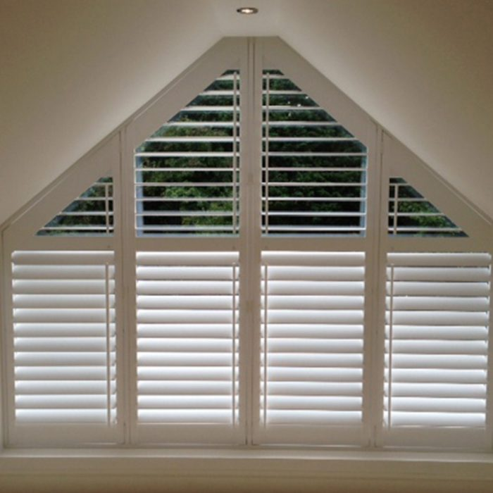 White wooden shutters fitted to triangular window frame