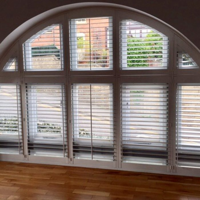 Plantation shutters fitted to arched window frame
