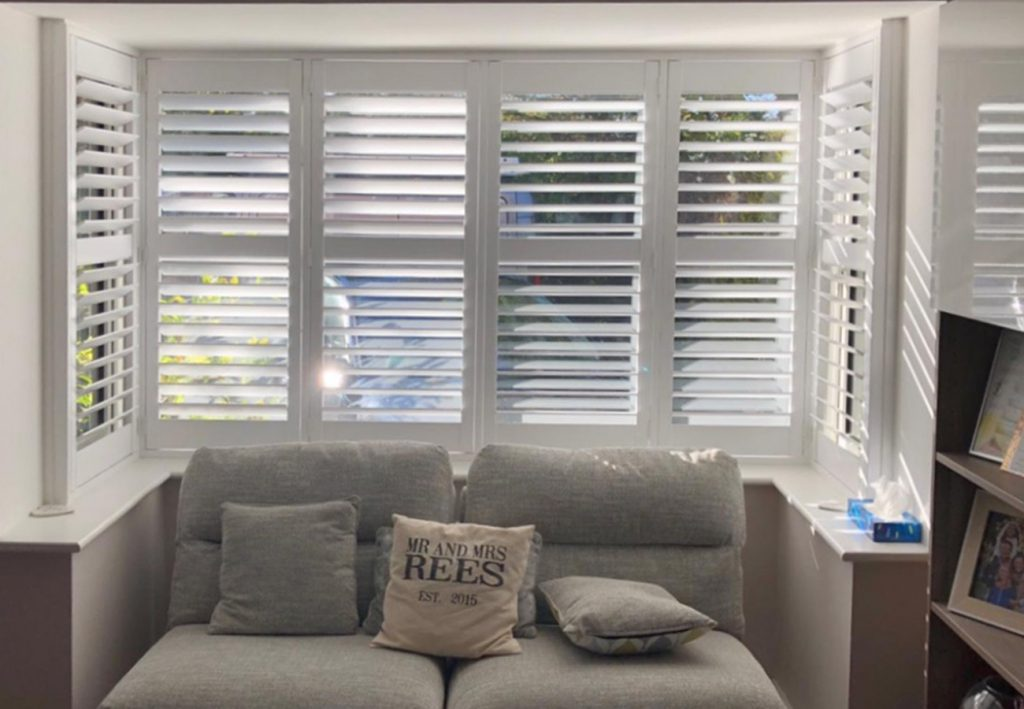 Plantation shutters in bay window with grey sofa