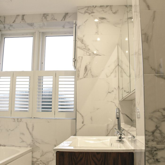 White marbled bathroom with wooden shutters half open
