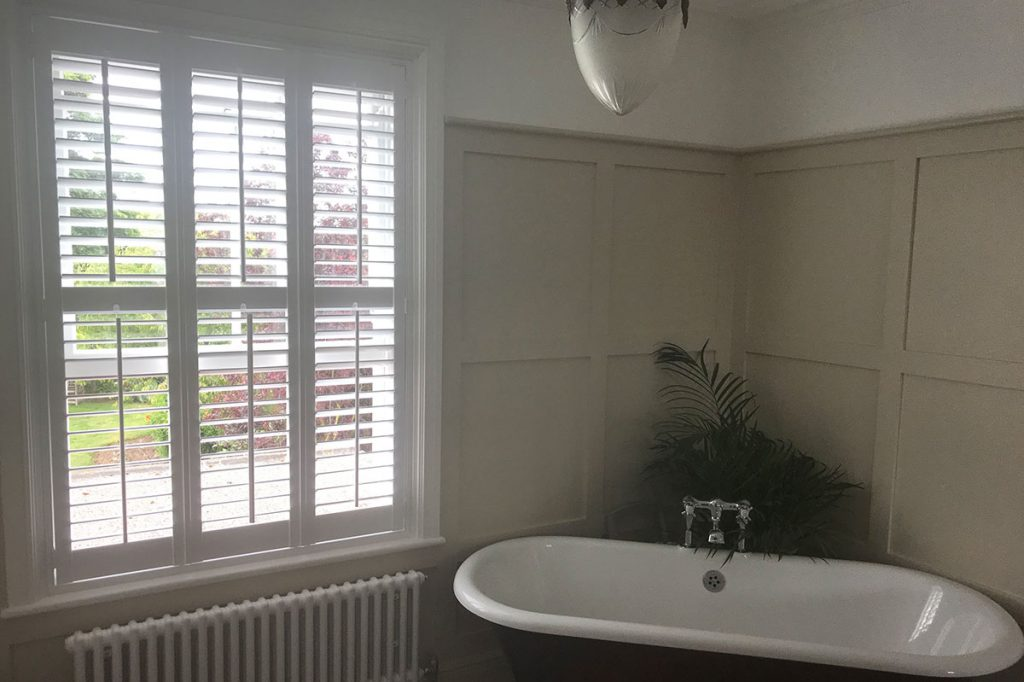 Roll top bath with plant and wooden shutters