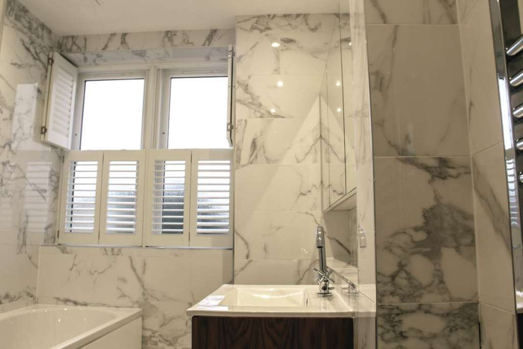 White marbled bathroom with half open wooden shutters