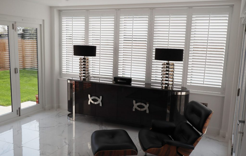 Matching lamps on luxury side board with plantation shutters