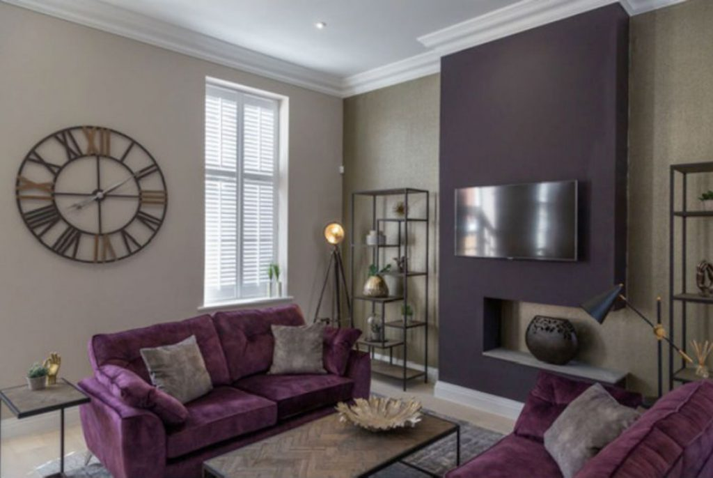 Purple chimney breast with sofas and tv on wall