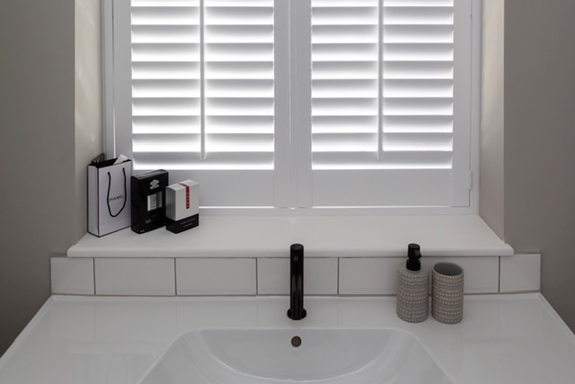 Black tap on white sink with plantation shutters