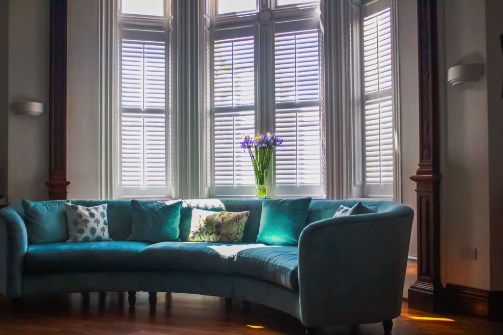 Curved turquoise sofa infront of white plantation shutters 2