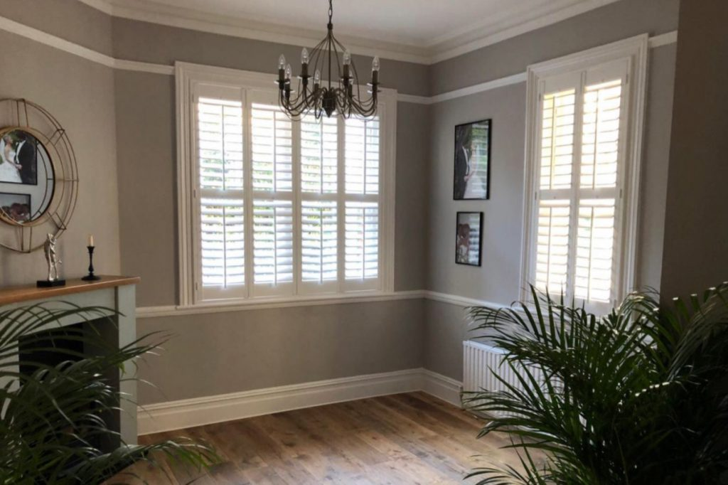 Grey walls with white window frames with shutters