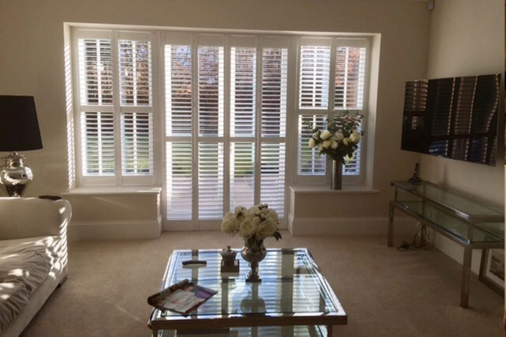 Folding plantation shutters in living room with TV