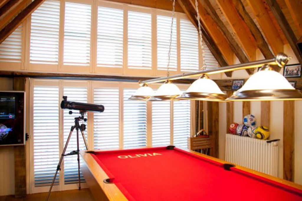 Two storey plantation shutters behind red pool table