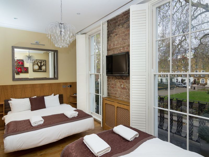 Floor to ceiling wooden shutters with TV on wall