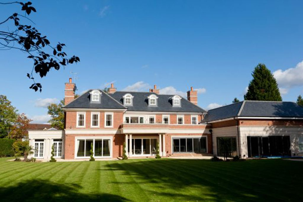 Back of large house with stripy lawn and topiary 2