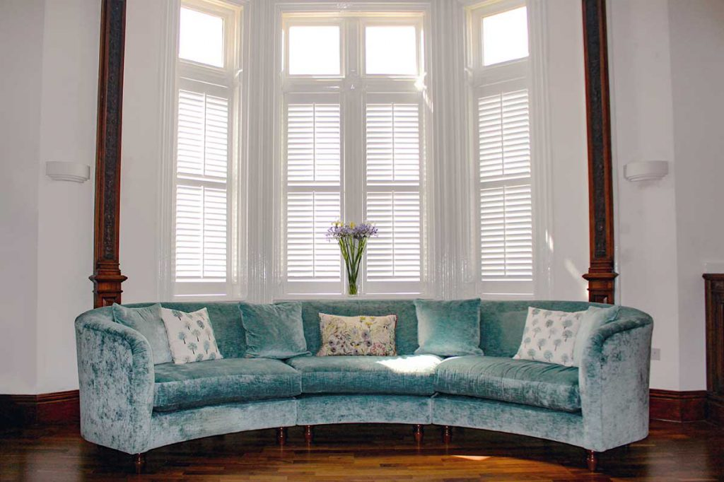 4 panels of wooden shutters in bay window with turquoise sofa