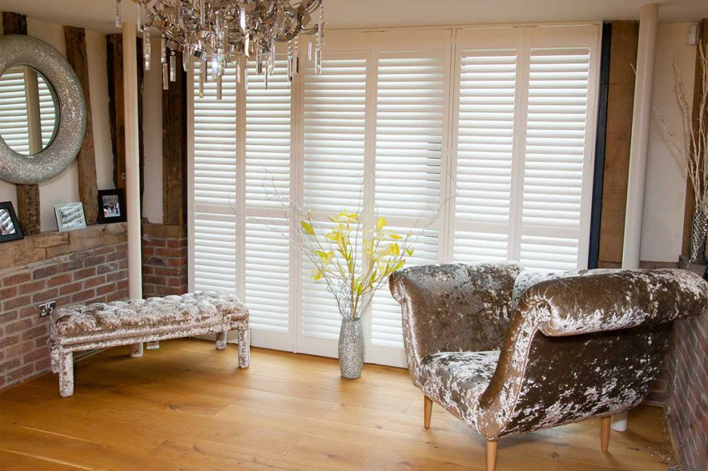 Foldable plantation shutters behind velvet armchair and stool