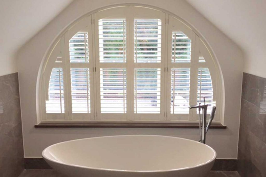 Luxury bath positioned infront of arched plantation shutters