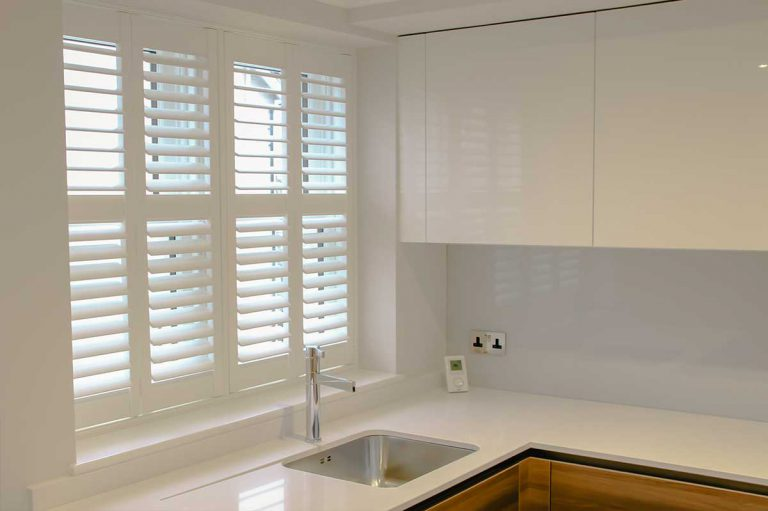 Modern kitchen with high gloss cupboards and wooden shutters