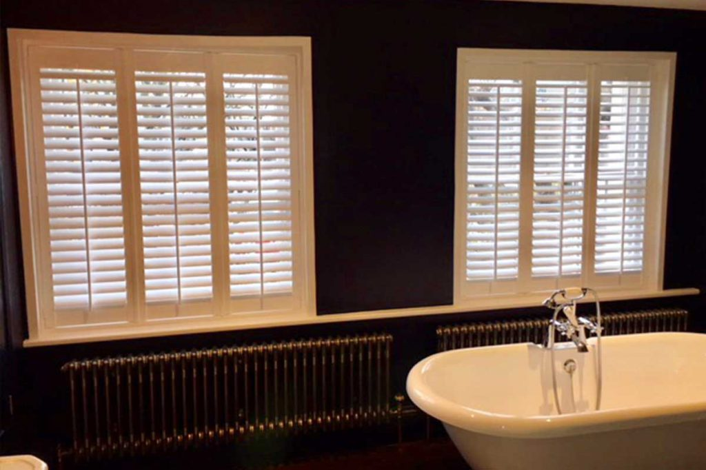 Black bathroom with white wooden shutters