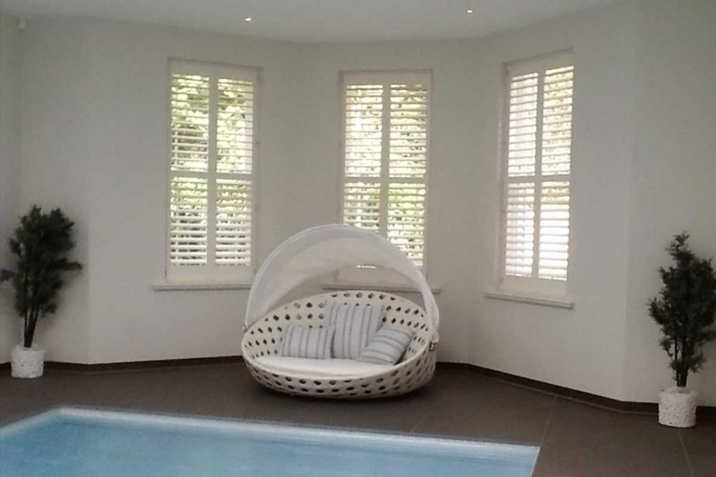 Lounger by indoor pool with plantation shutters