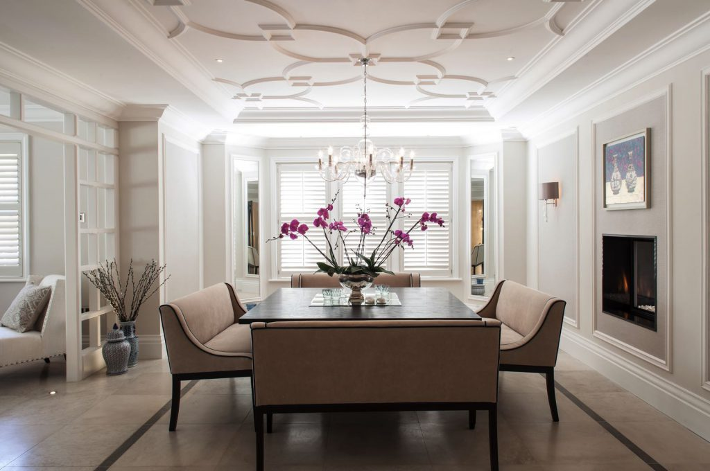 Dining table with orchid and long seats with shutters in background
