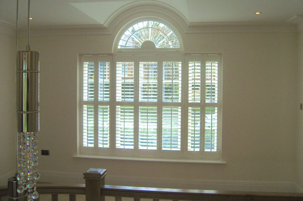 Window frame with small arch wooden shutters