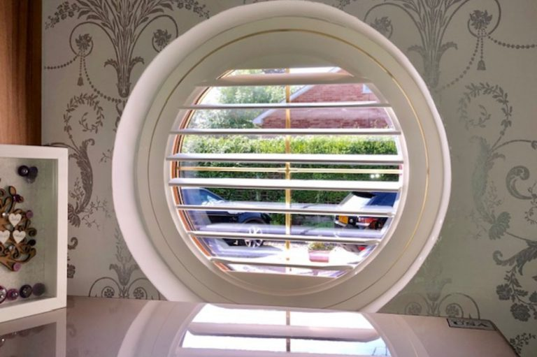 Round window frame with white plantation shutter