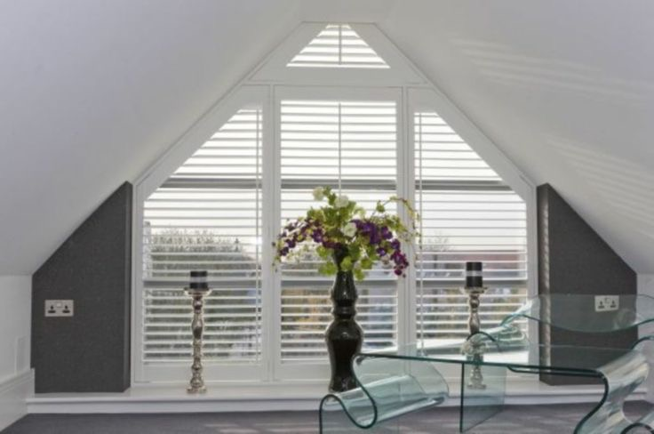 Triangular window frame with white wooden shutters fitted
