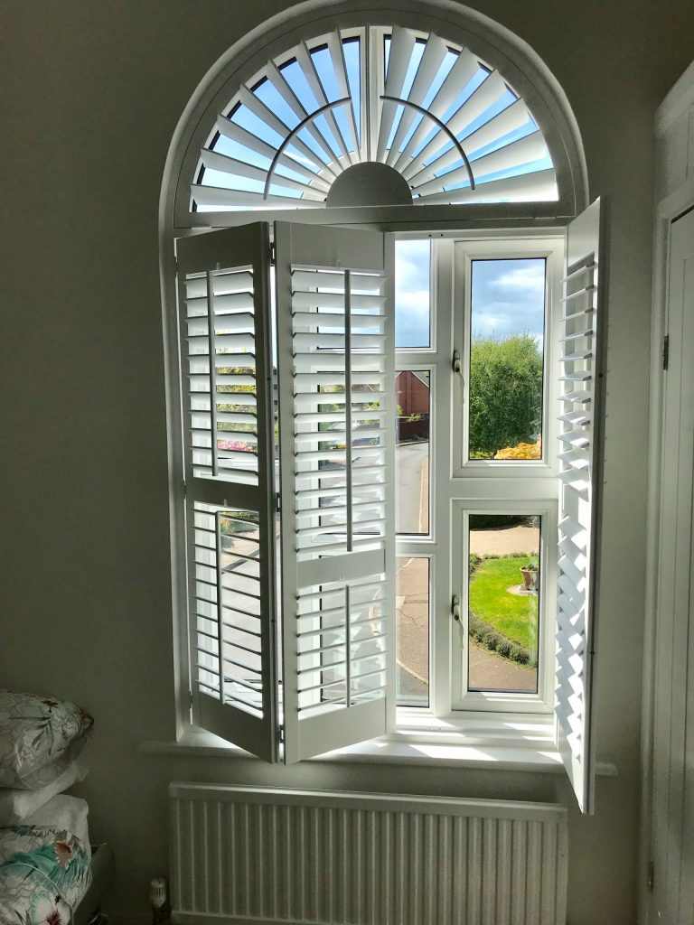 Folding wooden shutters with arched window frame