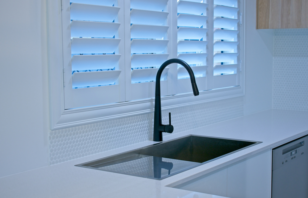 Kitchen sink next to with white plantation shutters