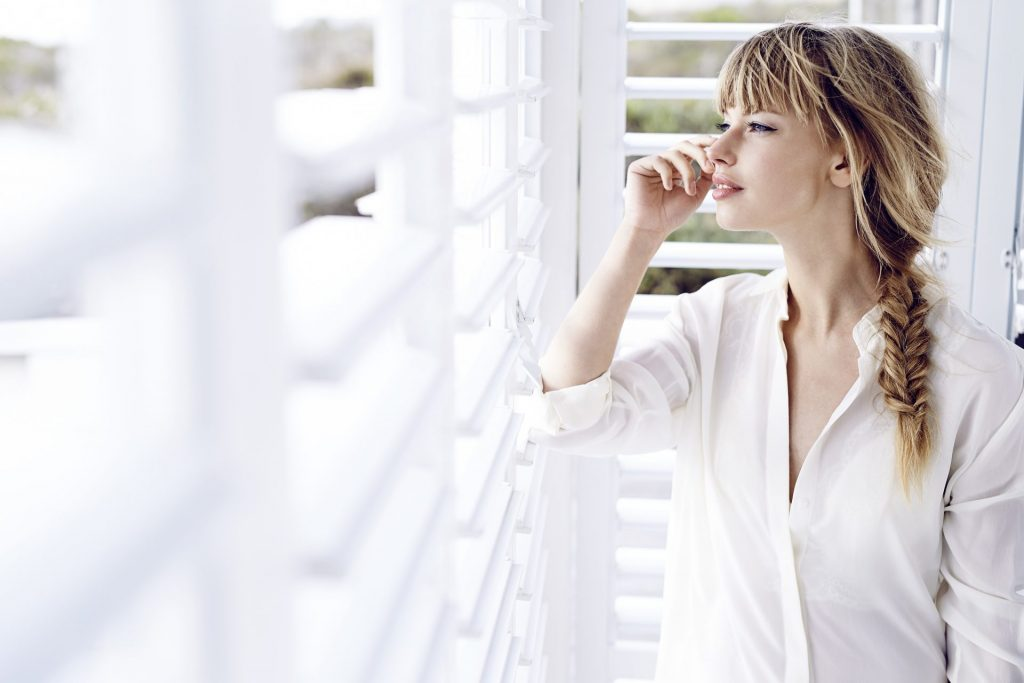 Girl looking out of white wooden shutters
