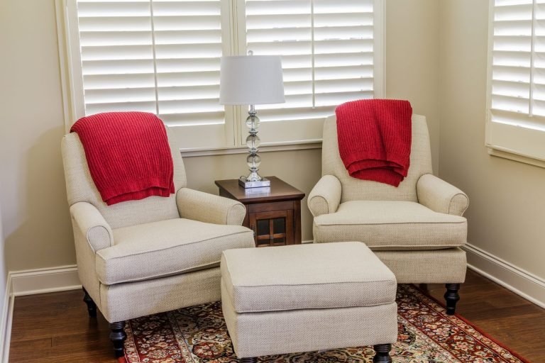 Two white arm chairs with red cusions infront of wooden shutters