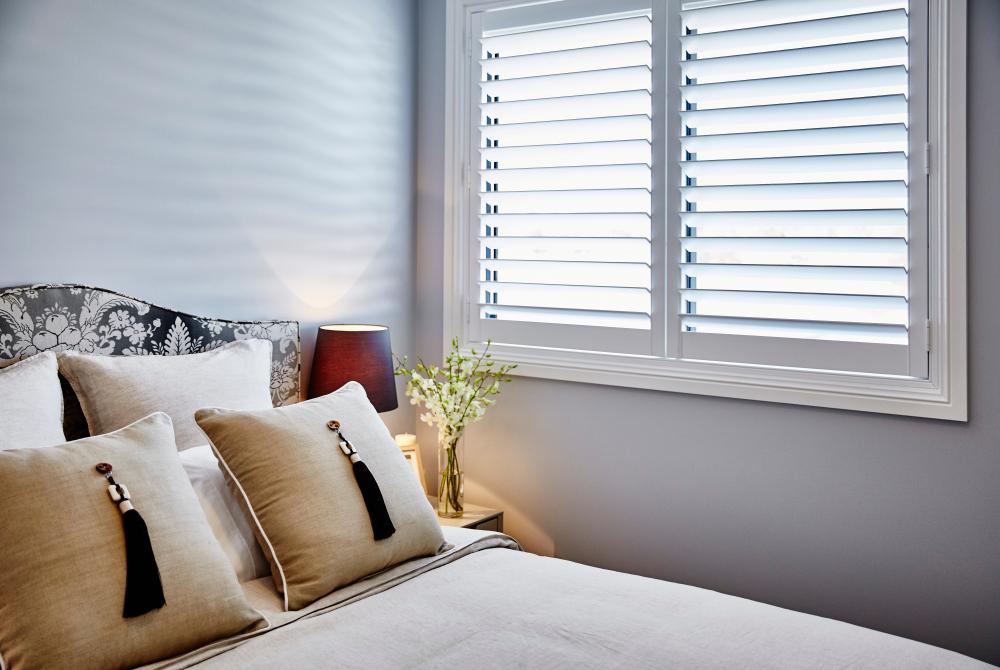 White wooden shuttters in modern white bedroom