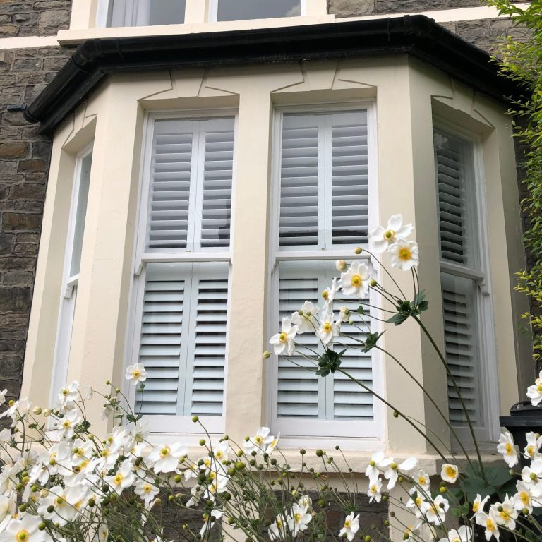 Bay window with white plantation shutters with flowers in foreground