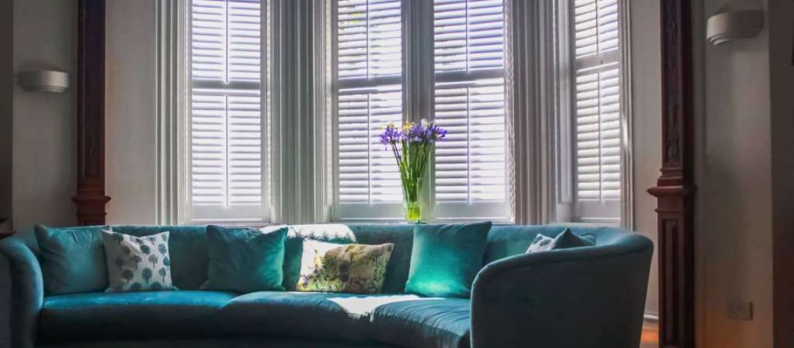 Curved turquoise sofa infront of white plantation shutters