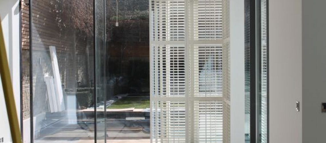 Plantation shutters over patio doors leading to garden
